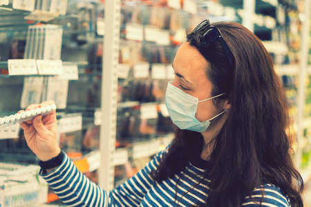 Woman in medical mask choosing goods in a store. Concept of shopping during quarantine at covid-19 pandemic. shopping at the time of the coronavirus. Beautiful young women in a flu mask. toned 免版税图像