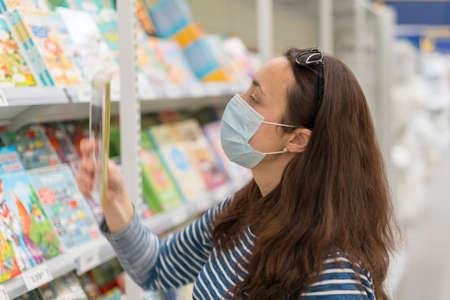 Woman in medical mask chooses books in the store. Concept of shopping during quarantine at covid-19 pandemic. shopping at the time of the coronavirus. Beautiful young women in a flu mask 免版税图像 - 152957638