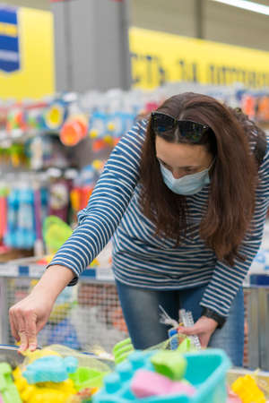 Woman in a protective mask in a supermarket chooses childrens toys. toned. vertical photo. toned 免版税图像 - 152957643