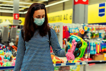 Woman in a protective mask in a supermarket chooses childrens toys. toned 免版税图像 - 152957645