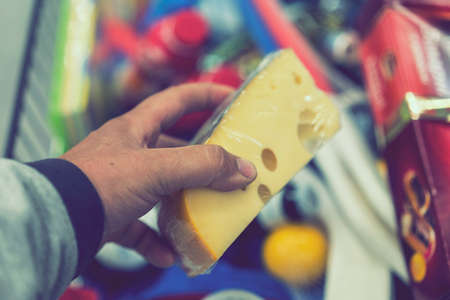 Male hand holds cheese in a supermarket. toned