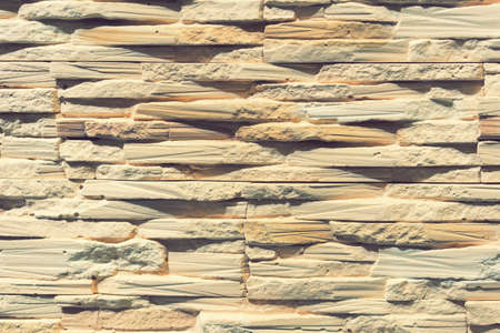 Stacked stone wall, natural stone cladding. Stone wall for background,Slab stone wall texture. Wall background of volcanic andesite basalt stone texture. toned 免版税图像 - 152957714
