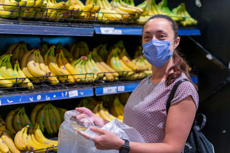 Focused woman in face mask choosing fruits, taking bananas from shelves in grocery store. Customer in supermarket. Side view. Shopping during epidemic concept 免版税图像 - 152957727