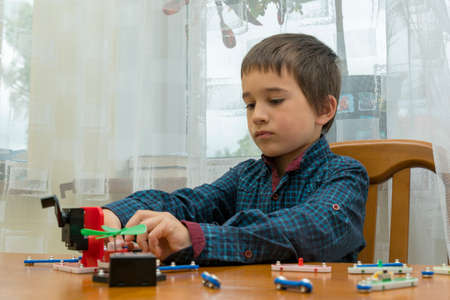 The boy playing an electric constructor. The child is played by intellectual toys. A boy in a blue shirt masters electronics. The concept of early development of children. toned 免版税图像 - 154869785