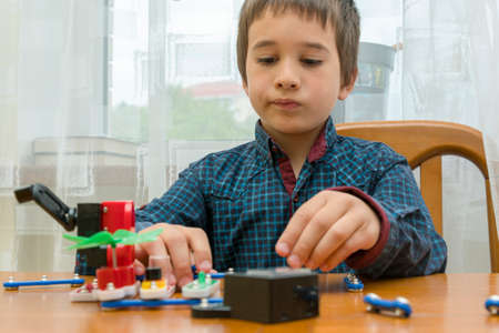 The boy playing an electric constructor. The child is played by intellectual toys. A boy in a blue shirt masters electronics. The concept of early development of children. toned