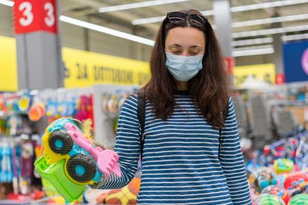 Woman in a protective mask in a supermarket chooses childrens toys. Woman in medical mask at the supermarket