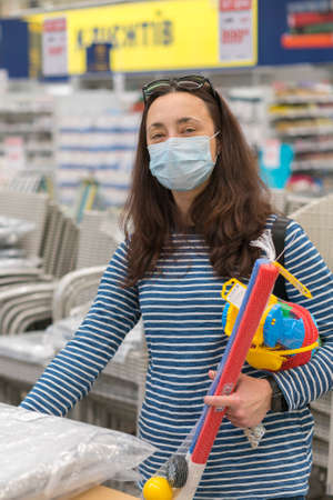 Woman in a protective mask in a supermarket chooses childrens toys. toned. vertical photo