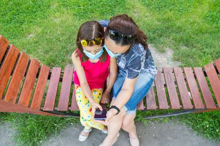 Mom with daughter in the park in medical masks. Family of mom and kid wearing protective medical mask for prevent virus outdoors in the park. new normal concept 免版税图像 - 154869797