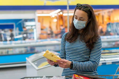 woman in protective medical mask in a supermarket chooses cheese. pandemic and covid-19 concept. Hand of the buyer with a piece of cheese in the store. toned