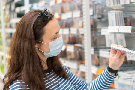 Woman in medical mask choosing goods in a store. Concept of shopping during quarantine at covid-19 pandemic. shopping at the time of the coronavirus. Beautiful young women in a flu mask