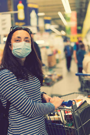 Asian young woman wearing a hygiene protective mask over her face while walking at the crowded shopping mall. Covid19 influenza in crowded place. woman wearing a mask in the supermarket. toned 免版税图像