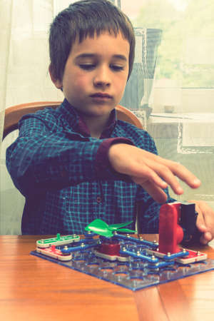 The boy playing an electric constructor. The child is played by intellectual toys. A boy in a blue shirt masters electronics. The concept of early development of children. vertical photo