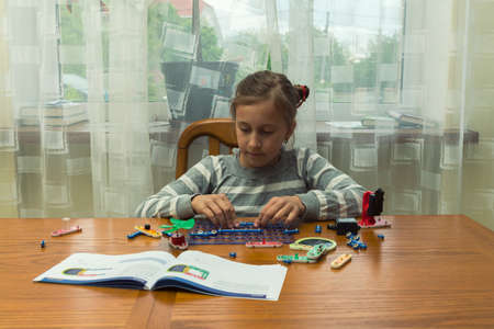 Positive lady playing with toy. She making it from constructor. Entertainment concept. Education, children, technology, science and futuristic concept. E-learning. toned