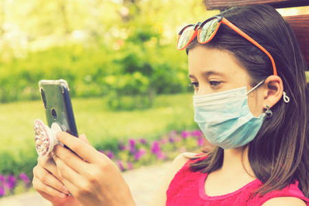 girl in protective mask holding a smartphone. teen girl siting on bench in green park with mobile phone. First stage of loosening coronavirus restrictions and self-isolation. toned