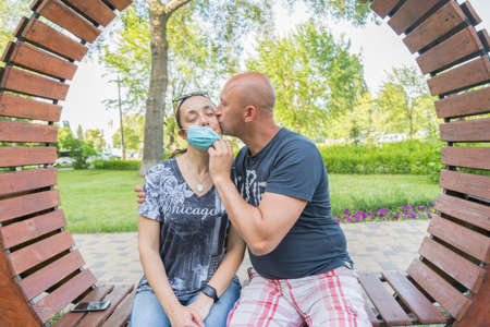Photo of a young and attractive couple kissing in the park while wearing reusable face masks. End of coronavirus pandemic, quarantine. Covid19 crisis is over