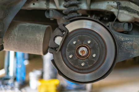The hub of a wheel in a car service. Suspended car with no wheels. Suspension of car in service room.The car lift up by lifter for maintenance suspension and cleaning parts. Close up Фото со стока