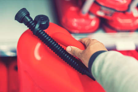 Red canister in the hands of a man. Concept of empty tank, problems with gasoline or diesel, refueling a car