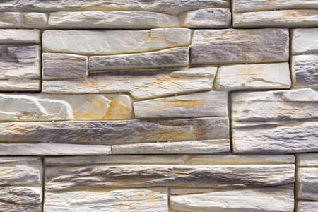 Stacked stone wall, natural stone cladding. Stone wall for background,Slab stone wall texture. Wall background of volcanic andesite basalt stone texture Фото со стока