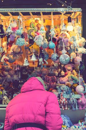 Woman choosing toys at Christmas market. woman chooses souvenirs at the Christmas market. back view. toned