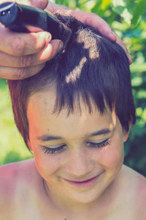 hand holds an electric hair clipper and cuts the boys long hair, barbershop at home, parent cuts hair while hairdressers are closed, stay home concept. vertical photo