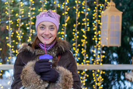 Beautiful woman in winter clothes with coffee in hand On the background of beautiful bokeh. outdoor