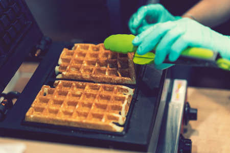 Waffle iron in the kitchen. Preparing homemade waffles, pouring a dough. Preparing of homemade waffles in twin waffle maker machine. Selective focus. toned