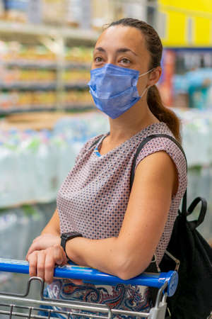 Alarmed female wears medical mask against virus while shopping in supermarket or store- health, safety and pandemic concept. Girl shopaholic in mall. vertical photo. toned. close up