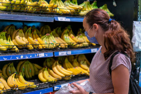 Focused woman in face mask choosing fruits, taking bananas from shelves in grocery store. Customer in supermarket. Side view. Shopping during epidemic concept. toned