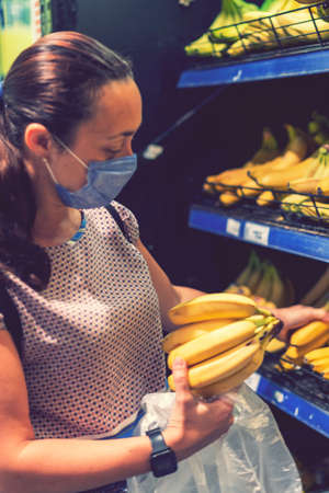 Focused woman in face mask choosing fruits, taking bananas from shelves in grocery store. Customer in supermarket. Side view. Shopping during epidemic concept. toned. vertical photo. toned.