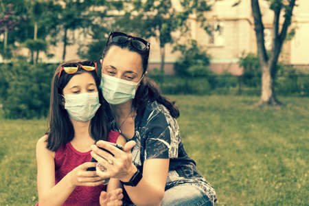 Mom with daughter in the park in medical masks. Family of mom and kid wearing protective medical mask for prevent virus outdoors in the park. new normal concept. copy space. toned