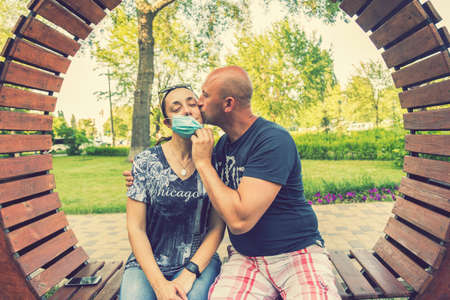 Photo of a young and attractive couple kissing in the park while wearing reusable face masks. End of coronavirus pandemic, quarantine. Covid19 crisis is over. toned Фото со стока