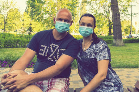 Happy couple in love wearing medical mask to protect from coronavirus. Park outdoors, coronavirus quarantine. Couple in love, man and woman looking each other in protective medical maskes. toned