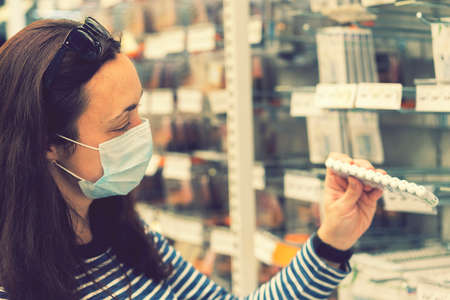 Woman in medical mask choosing goods in a store. Concept of shopping during quarantine at covid-19 pandemic. shopping at the time of the coronavirus. Beautiful young women in a flu mask. toned Фото со стока