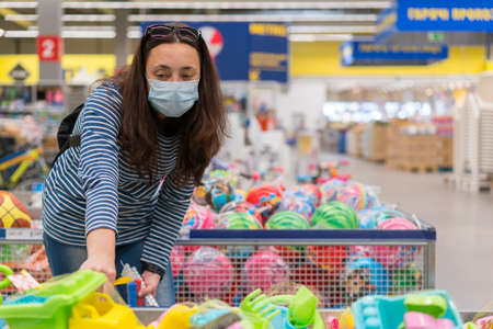 Woman in a protective mask in a supermarket chooses childrens toys. Woman in medical mask at the supermarket toned Фото со стока