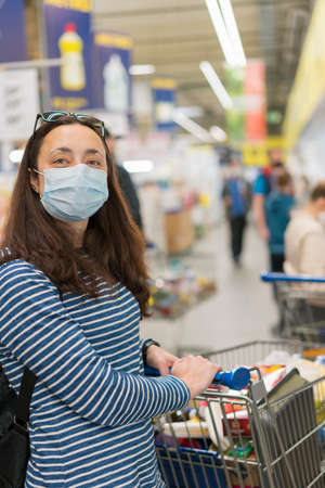 Asian young woman wearing a hygiene protective mask over her face while walking at the crowded shopping mall. Covid19 influenza in crowded place. woman wearing a mask in the supermarket. verical photo Фото со стока