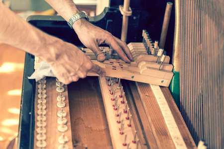 Closeup of hand and tools of tuner working on grand piano.