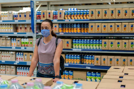 Alarmed female wears medical mask against virus while grocery shopping in supermarket or store- health, safety and pandemic concept Фото со стока