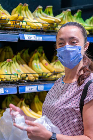 Focused woman in face mask choosing fruits, taking bananas from shelves in grocery store. Customer in supermarket. Side view. Shopping during epidemic concept. vertical photo Фото со стока