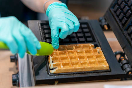 Waffle iron in the kitchen. Preparing homemade waffles, pouring a dough. Preparing of homemade waffles in twin waffle maker machine. Selective focus