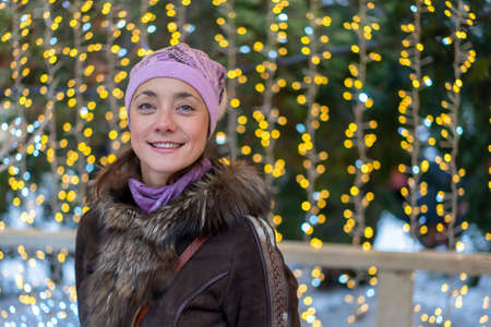 smiling young woman wearing winter clothes celebrating Christmas at the street with sparklers
