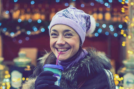 Beautiful young woman with coffee cup in the city. Beautiful woman with coffee on the street in winter clothes. Woman Having Hot Drink Outdoors On Winter Market. toned Фото со стока