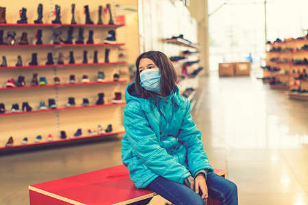 Young girl face mask chooses new shoes in a family store. Shopping time with kids during virus outbreak. Shopping entertaiment. Precautions during the pandemic. toned