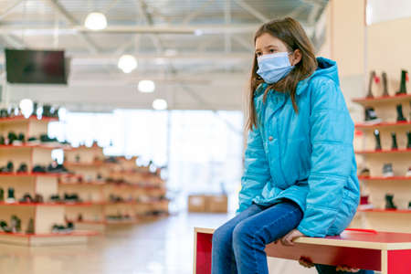 Young girl face mask chooses new shoes in a family store. Shopping time with kids during virus outbreak. Quarantine over. Shopping entertaiment. Precautions during the pandemic