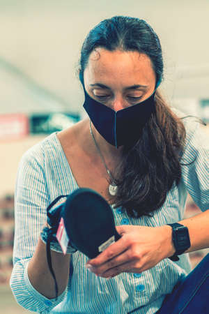 woman wearing face protective medical mask for protection from virus disease in shoes store during pandemic. Woman during a pandemic. vertical photo. toned