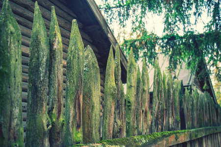 ancient style wooden wall Palisade. High wooden antique palisade. Fence made of sharp wooden stakes on the background of logs. ancient style wooden wall Palisade. toned Фото со стока