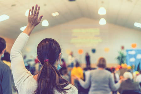 People praying in a church. soft focus of christian people group raise hands up worship God Jesus Christ together in church. toned
