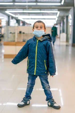 Toddler child, boy, wearing protective medical mask in shopping center during  pandemic. The child wears a protective mask in the store