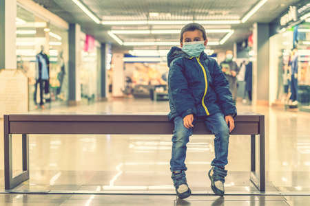 Toddler child, boy, wearing protective medical mask in shopping center during pandemic. The child wears a protective mask in the store. toned