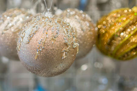 beautiful golden christmas balls on a golden background. Christmas balls close up picture. toned Фото со стока