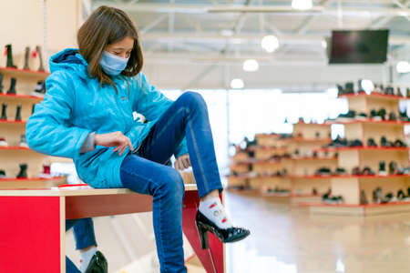 Young girl face mask chooses new shoes in a family store. Shopping time with kids during outbreak. Shopping entertaiment. Precautions during the coronavirus pandemic Фото со стока